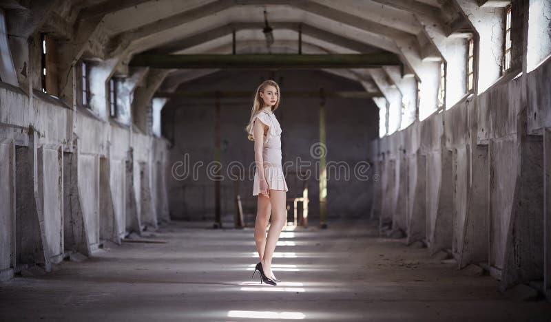 Hembra rubia atractiva en el vestido poner crema fotos de archivo