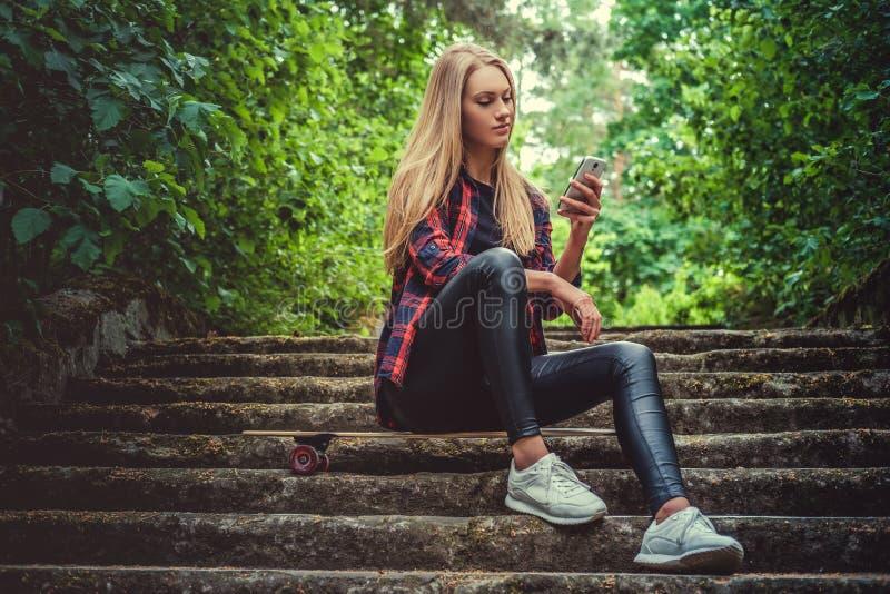 Hembra rubia casual con longboard usando smartphone imagen de archivo libre de regalías
