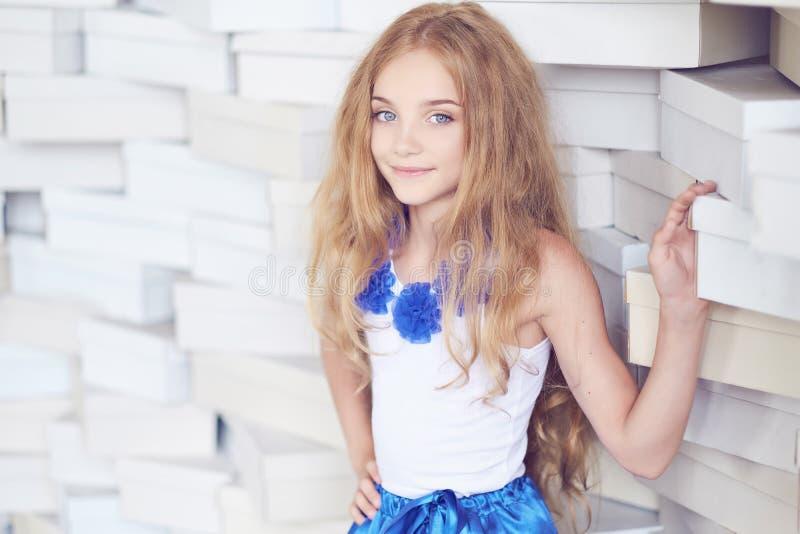 Hembra rubia linda del adolescente en una falda azul imagen de archivo libre de regalías