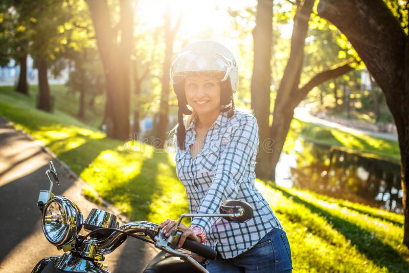 Hembra rubia sonriente en vaqueros, camiseta y casco imagen de archivo