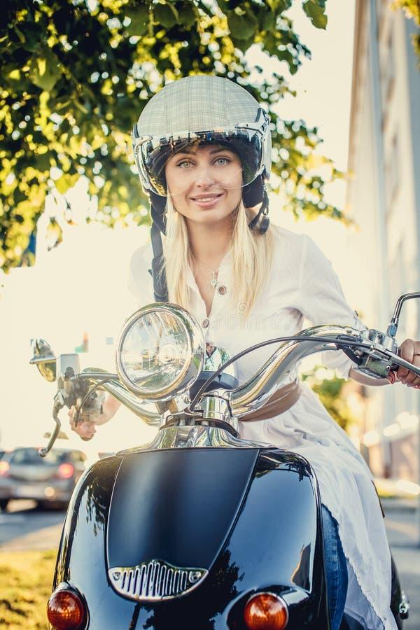 Hembra rubia sonriente en vaqueros, camiseta y casco imágenes de archivo libres de regalías