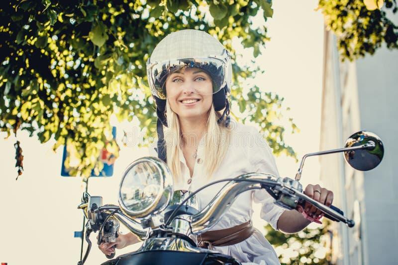 Hembra rubia sonriente en vaqueros, camiseta y casco fotos de archivo libres de regalías