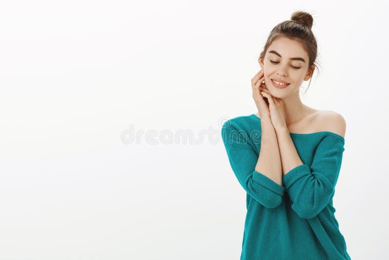 Hembra sensual y blanda femenina con el peinado del bollo en el suéter flojo elegante, tocando suavemente la cara y sonriendo mie imagen de archivo