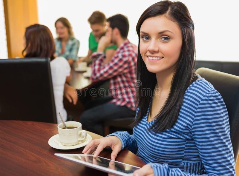Hembra sonriente con café usando la tableta en la cafetería imágenes de archivo libres de regalías