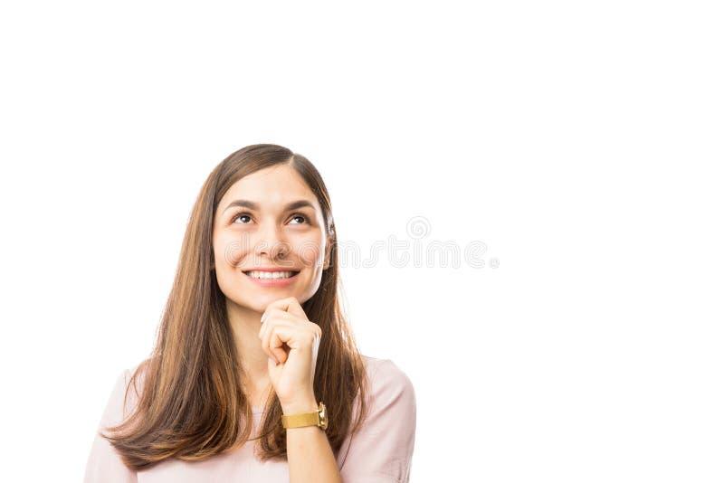 Hembra sonriente con la mano en Chin Looking At Empty Space imagen de archivo libre de regalías