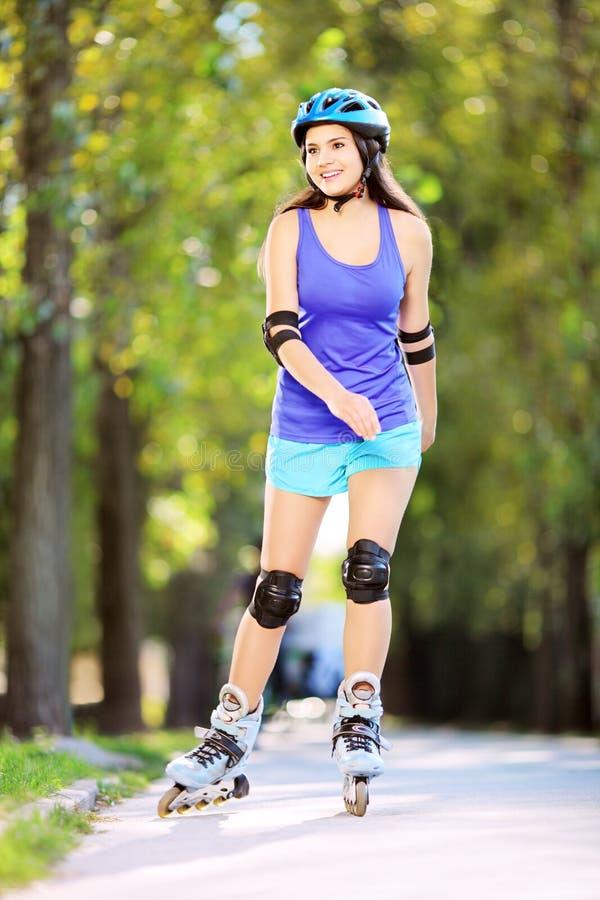 Hembra sonriente de los jóvenes en el patinaje de rodillos en un parque fotografía de archivo libre de regalías