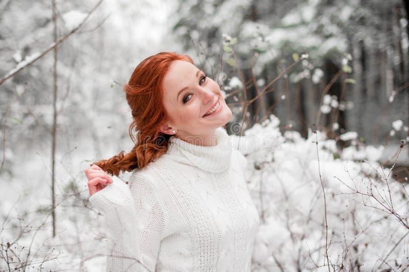 Hembra sonriente del jengibre en el suéter blanco en la nieve diciembre del bosque del invierno en parque Retrato Tiempo lindo de imagen de archivo libre de regalías