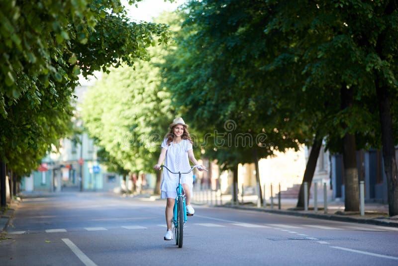 Hembra sonriente en el sombrero blanco del vestido y de paja que monta la calle ancha verde de la ciudad del dow de la bici azul imagenes de archivo