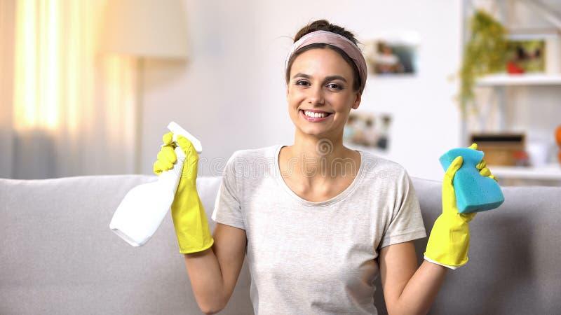 Hembra sonriente en los guantes que muestran el espray y la esponja de limpiamiento a la cámara, quehacer doméstico fotos de archivo libres de regalías