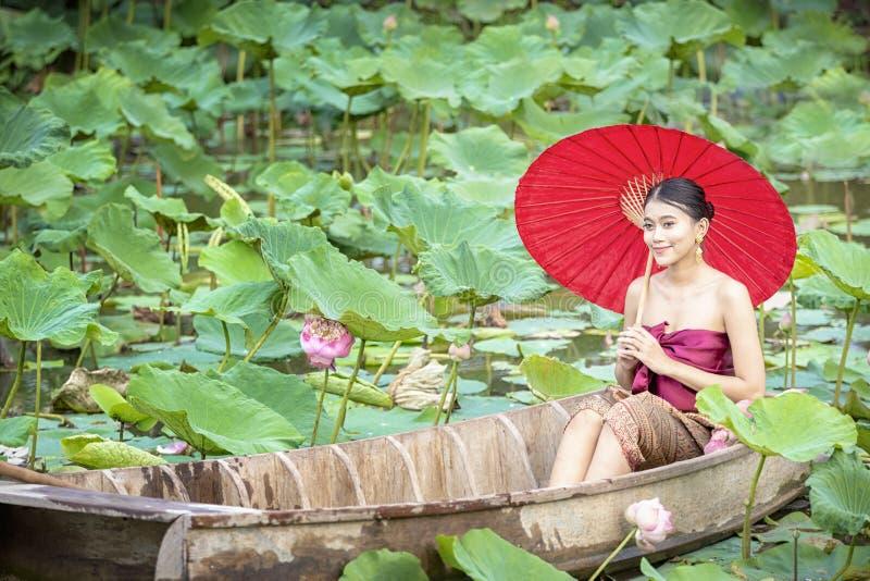 Hembra tailandesa en un barco de madera que recoge las flores de loto Mujeres asiáticas que se sientan en los barcos de madera pa foto de archivo