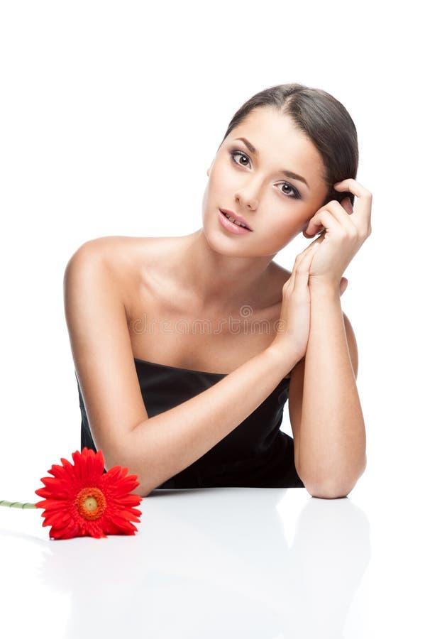 Hembra triguena joven con la flor del gerbrera fotografía de archivo