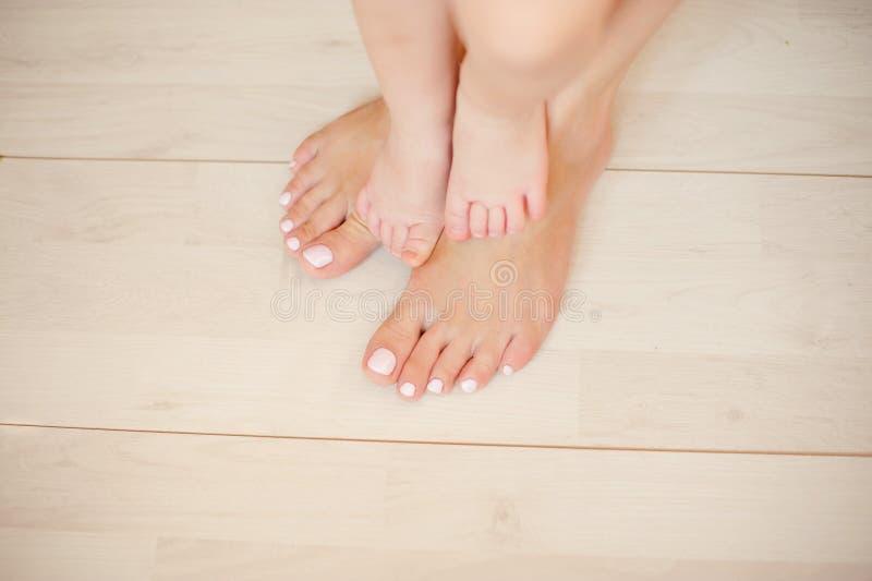 Hembra y children& hermosos x27; pies de s en un piso ligero imagenes de archivo