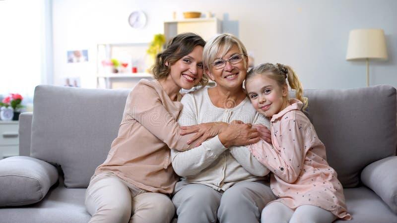 Hembras multigeneraciones que abrazan en la c?mara sonriente del sof? casero, proximidad de la familia fotos de archivo libres de regalías