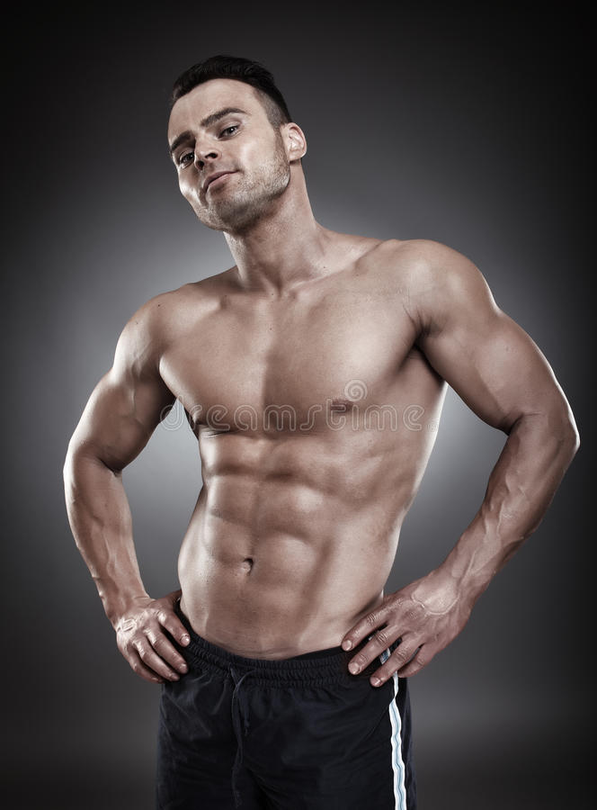 Hemdloser athletischer Mann, der in die Seite gestemmt steht stockbild