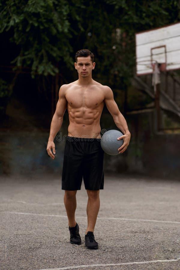 Hemdloser, athletischer, muskulöser Kerl mit Ball in den Händen, sitzend auf einem Basketballplatz, auf einem Straßenhintergrund lizenzfreie stockfotografie