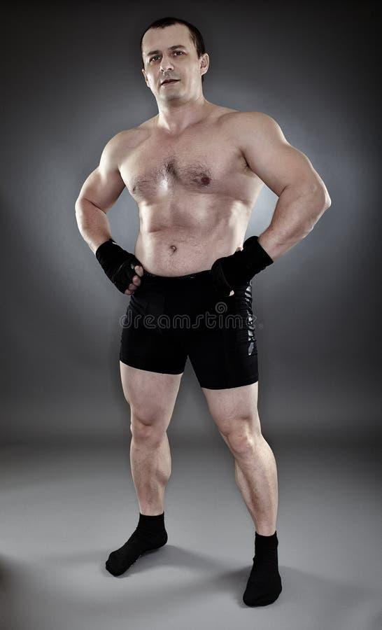 Hemdloser athletischer muskulöser Mann, der in die Seite gestemmt steht stockbilder