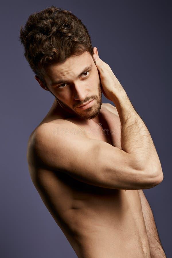 Hemdloser attraktiver ernster Mann, der sein Gesicht überprüft stockfotos