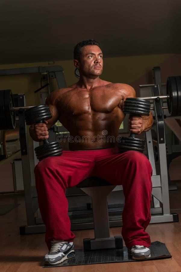 Hemdloser Bodybuilder, der mit Dummkopf an der Bank aufwirft lizenzfreie stockfotos