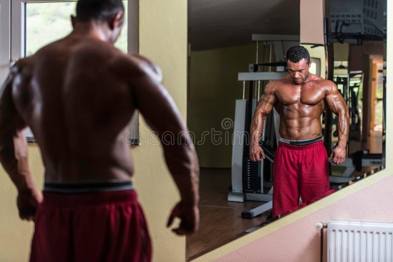 Hemdloser Bodybuilder, der am Spiegel aufwirft lizenzfreies stockfoto