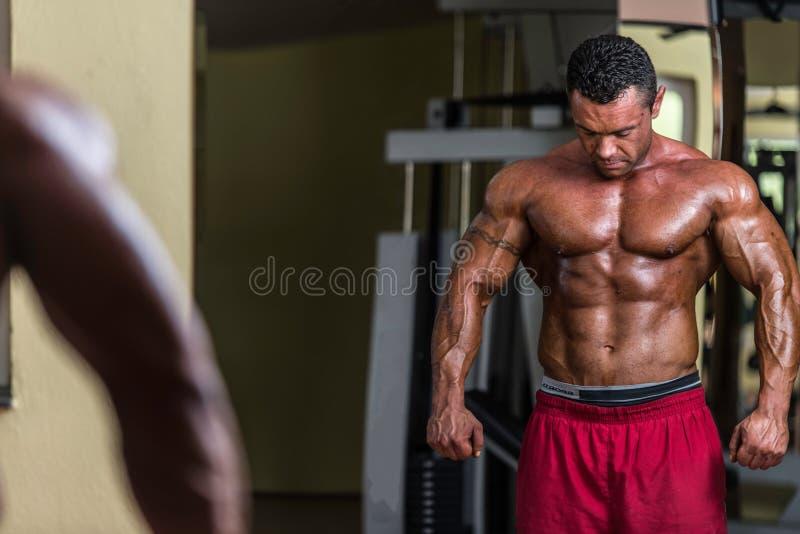 Hemdloser Bodybuilder, der am Spiegel aufwirft lizenzfreies stockbild