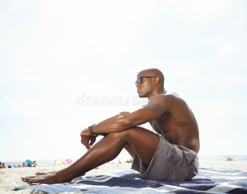 Hemdloser junger Mann, der auf dem Strand weg schaut sitzt lizenzfreie stockbilder