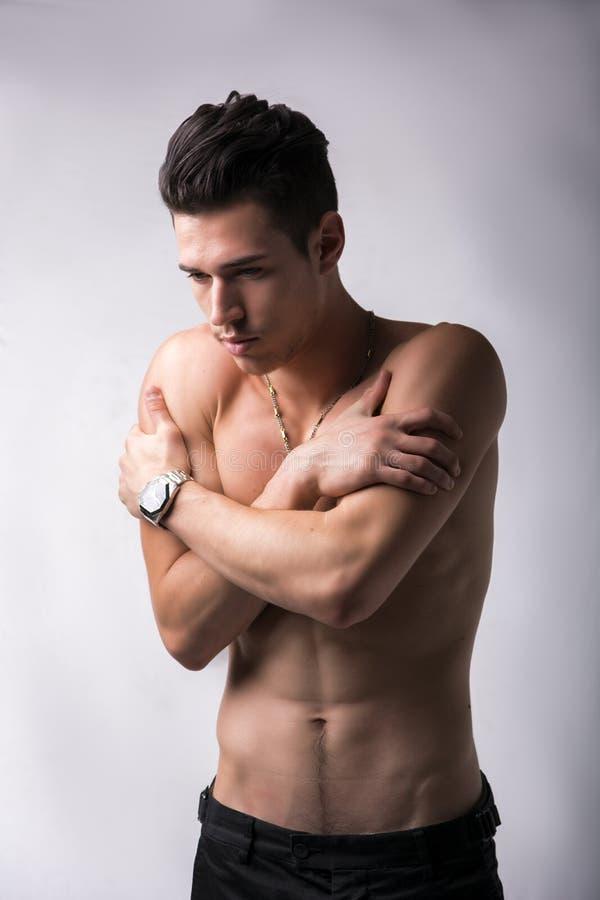 Hemdloser junger Mann, der sich umarmt stockfotos