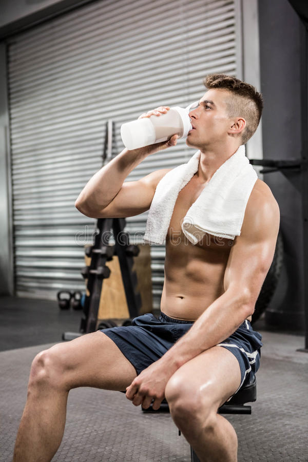 Hemdloser Mann auf trinkendem Proteindrink der Bank lizenzfreie stockfotografie