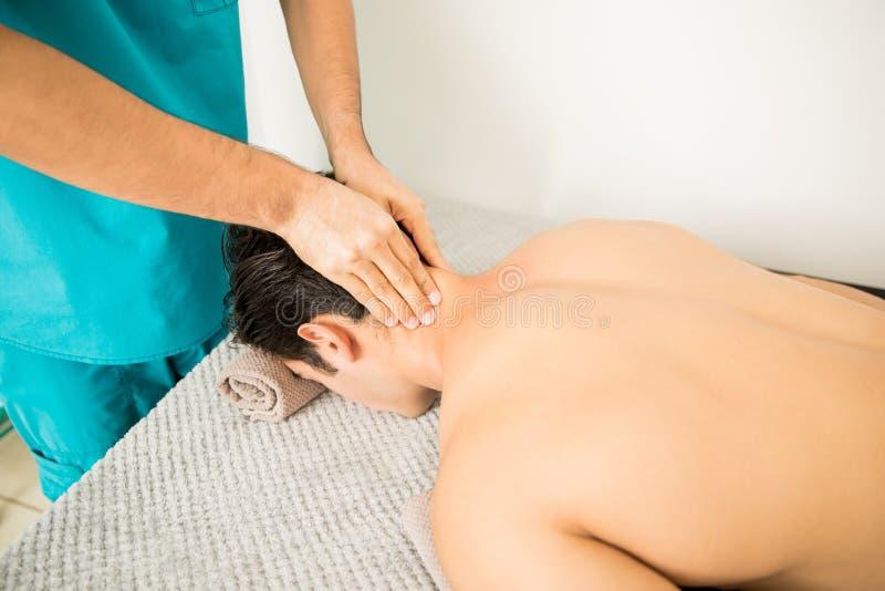 Hemdloser Mann, der Hals-Massage vom Therapeuten In Hospital empfängt lizenzfreie stockbilder