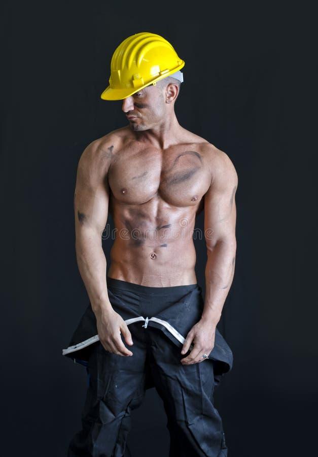 Hemdloser muskulöser Bauarbeiter tragender Overall und Hardhat lizenzfreie stockfotos