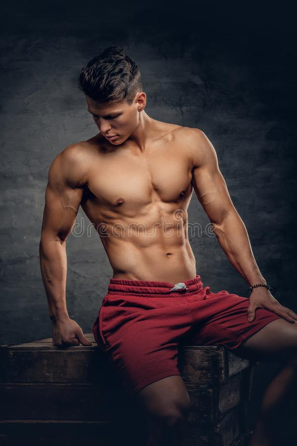 Hemdloser muskulöser Mann auf grauem Hintergrund stockbild