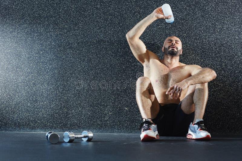 Hemdloser Sportler, der auf dem Boden erneuert nach Training sitzt lizenzfreie stockfotografie