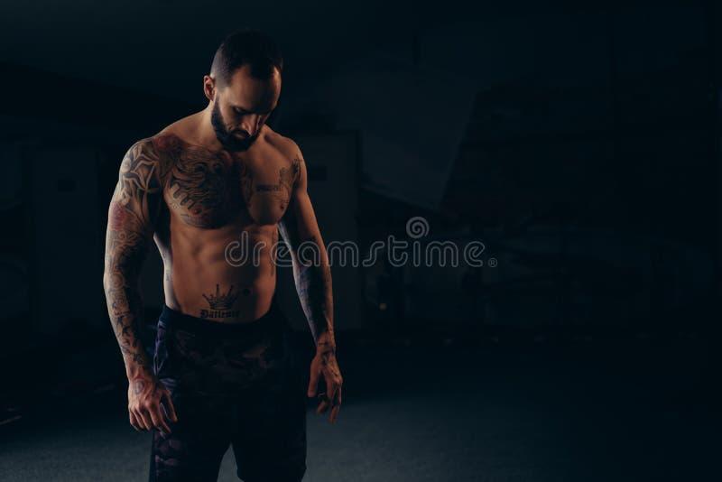 Hemdloser starker männlicher Athlet, der zum Boden schaut stockfoto