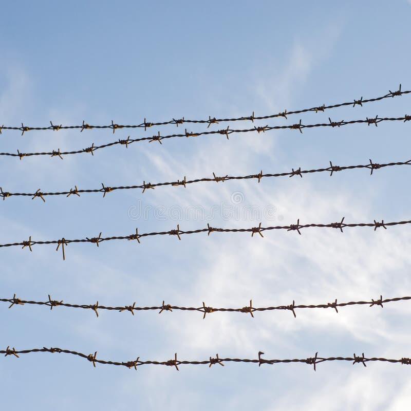 Hemel achter prikkeldraadomheining Gevangenismuur stock afbeelding