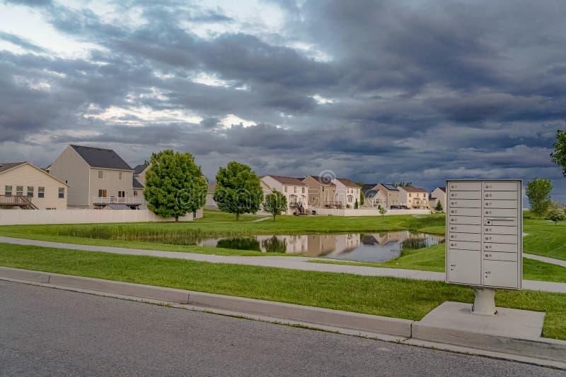 Hemel die met grijze wolken over huizen en vijver amid een enorm grasrijk terrein wordt gevuld stock foto