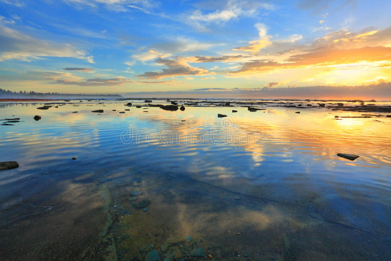 Hemel en Aarde het nadenken Ochtendhemel in de oceaan wordt weerspiegeld die stock foto