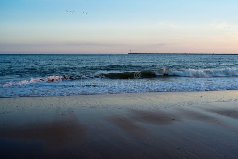 Hemel, golven en zand in het strand stock foto