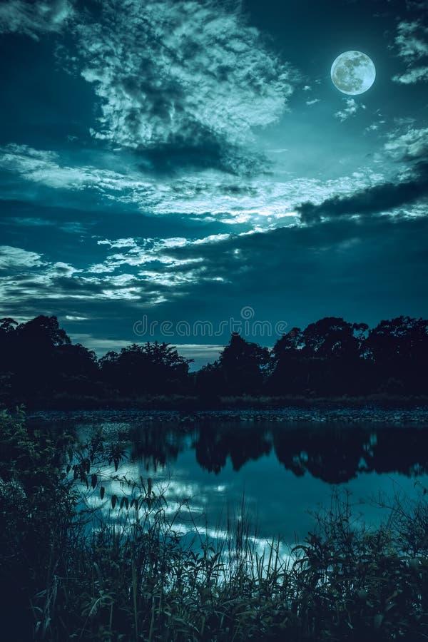 Hemel met donkere bewolkt en volle maan boven silhouetten van bomen en rustig meer royalty-vrije stock fotografie