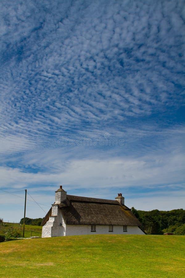 Hemel over mooi steenplattelandshuisje stock afbeeldingen