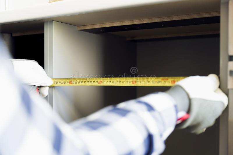 Hemförbättring och inredesignbegrepp Leverantör som tar mått av ett splitterny köksskåp arkivfoto