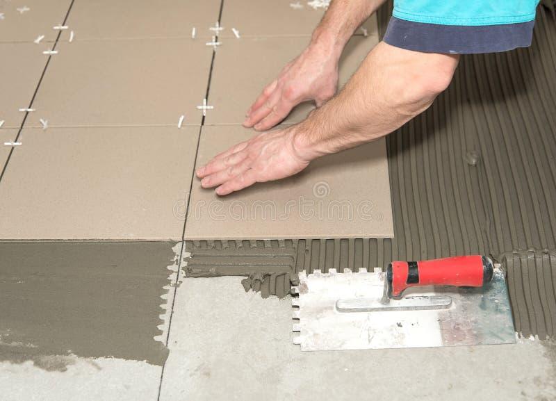 Hemförbättring renovering Byggnadsarbetaren belägger med tegel, den keramiska tegelplattan arkivfoton
