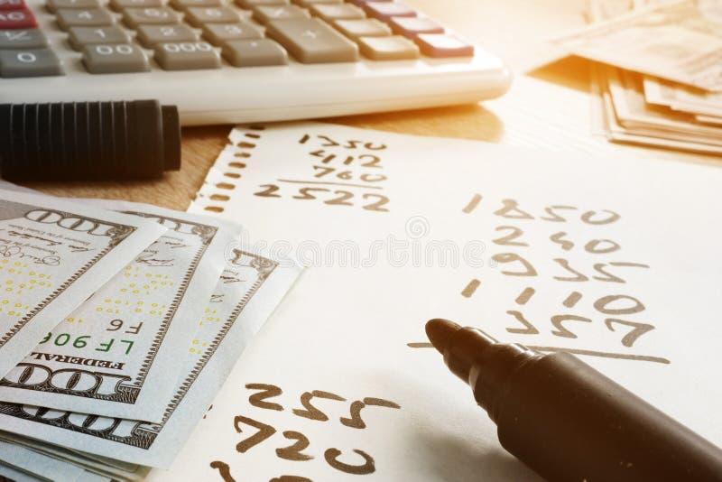 Hemfinanser Papper med beräkningar, räknemaskinen och pengar arkivbilder