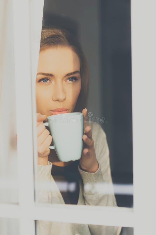 Hemhjälpen kopplar av med kaffe fotografering för bildbyråer