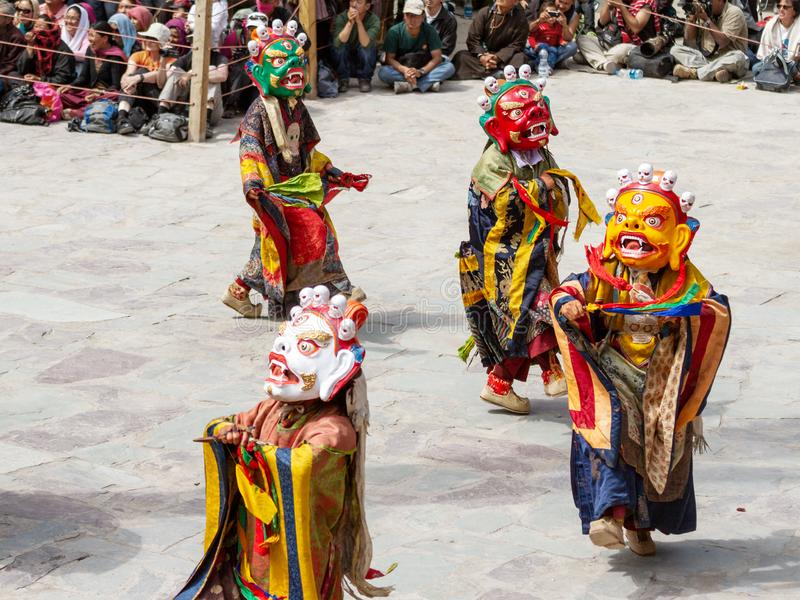 Monks in dharmapala mask with ritual edged weapons perform a religious masked and costumed mystery dance of Tantric Tibetan royalty free stock photos