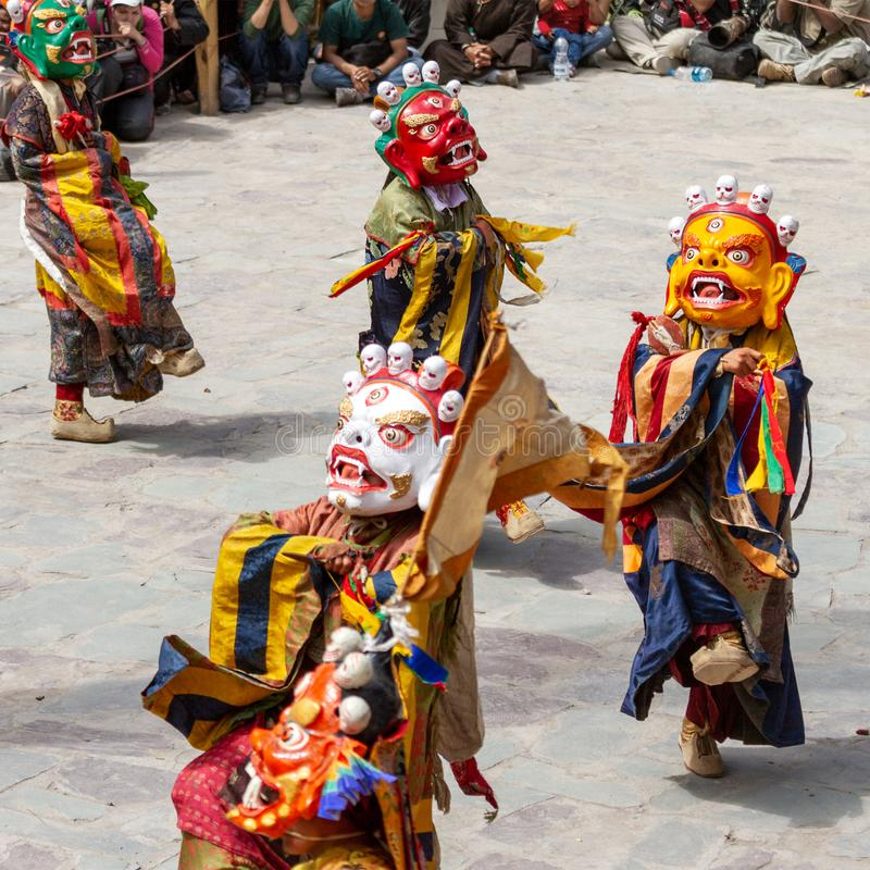 Monks in dharmapala mask with ritual edged weapons perform a religious masked and costumed mystery dance of Tantric Tibetan royalty free stock images