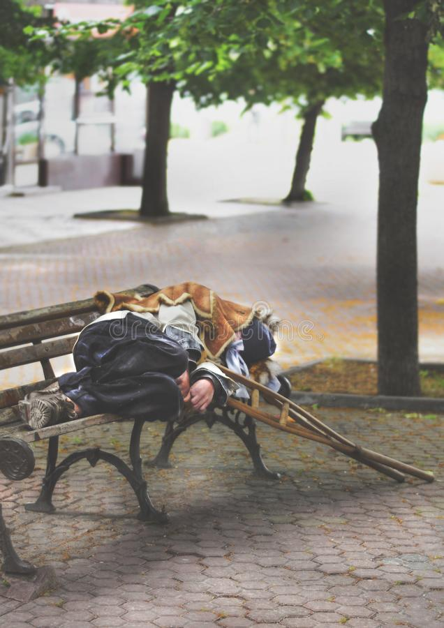Hemlös gamal man som sover på en bänk arkivbilder
