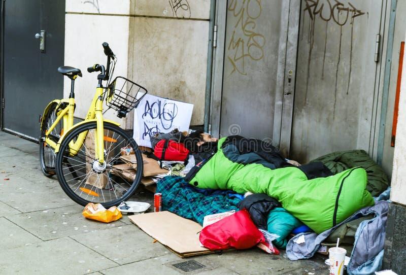 Hemlös man med cykeln och sovsäcken sovande i dörröppning i södra Kennsington London UK 1-10-2018 arkivbild