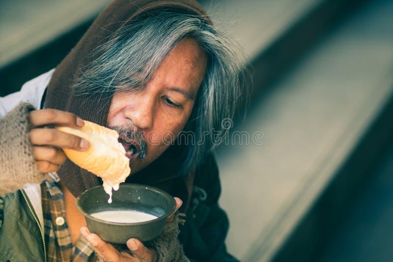 Hemlös man på trappan av gångbanagatan i staden som äter bröd och att mjölka formvänlighetfolk för att ge honom royaltyfri foto