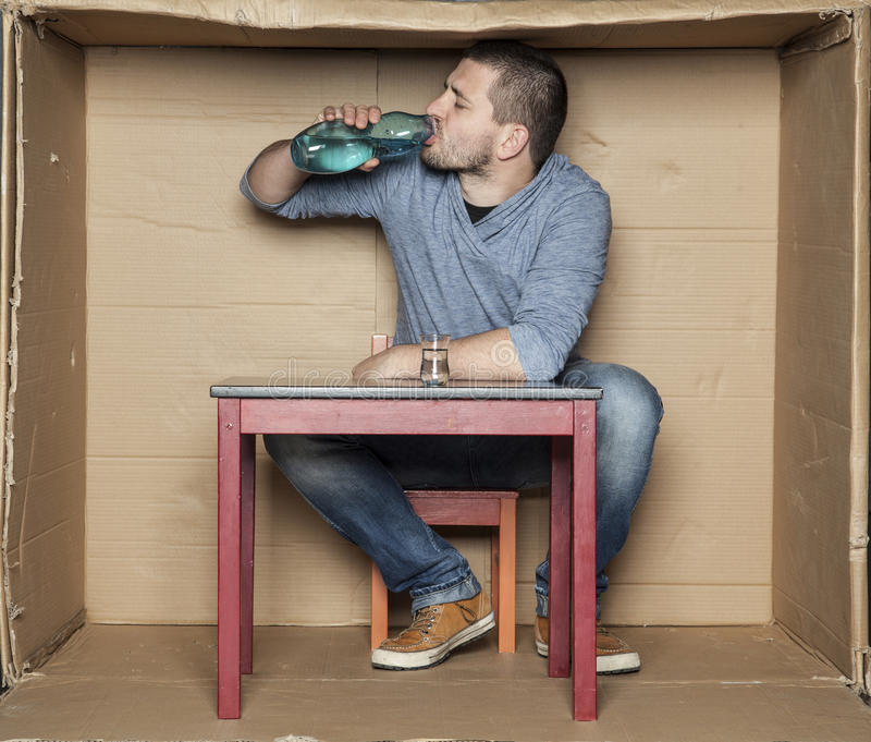 Hemlös man som dricker alkohol från en flaska arkivbilder