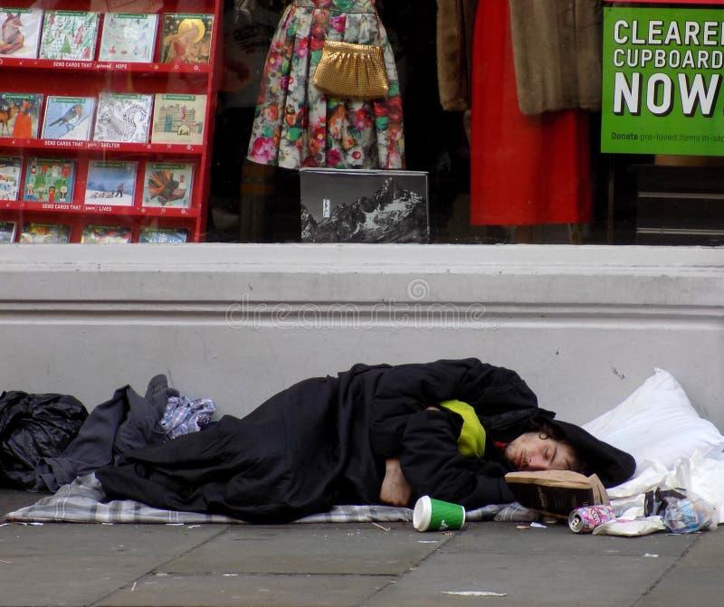 Hemlös man som sover buse på gatan royaltyfri bild
