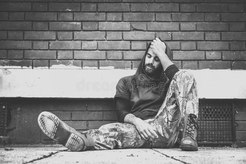 Hemlös mandrog och alkoholknarkare som bara sitter och som är deprimerad på gatan som lutar mot en vägg för byggnad för röd tegel arkivbild